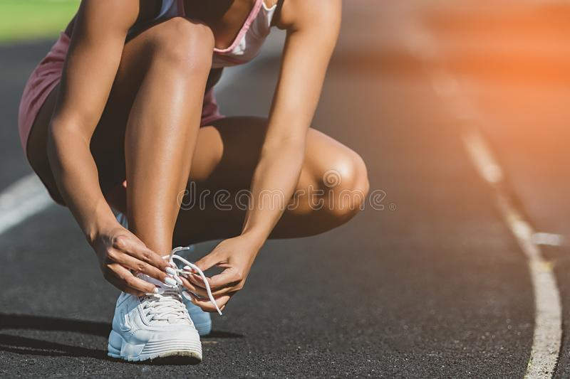 Woman`s hand tying shoe laces at stadium. Preparation for running. Close up. sunshine background royalty free stock image