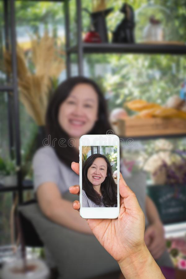 Woman`s hand using smart phone take a picture an asian women smile happily. stock photos