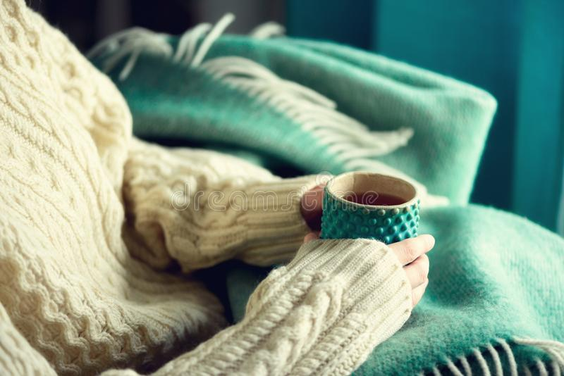 Woman`s hand in woolen sweater holding cup of tea with lemon on a cold day. Copy space. Winter and Christmas holidays royalty free stock image