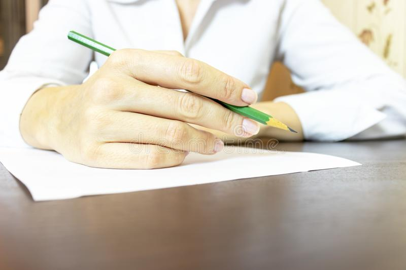 Woman`s hand writing something on paper close up. Unrecognizable business woman in white shirt writing with a pencil royalty free stock photos