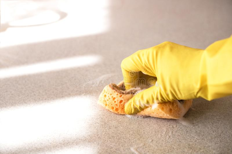 Woman`s hand with sponge cleaning the table. stock image
