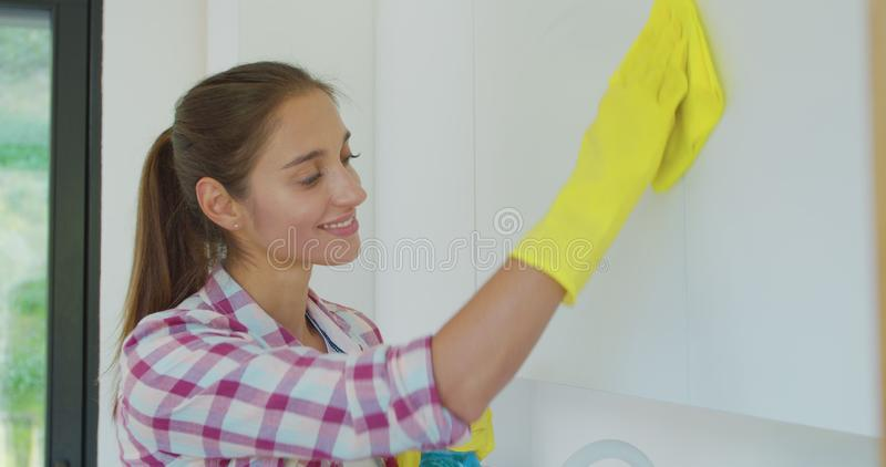 Woman`s hand in a yellow rubber glove cleans the shiny surface of a modern plastic kitchen Cabinet with a cloth. The stock image
