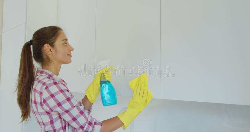 Woman`s hand in a yellow rubber glove cleans the shiny surface of a modern plastic kitchen Cabinet with a cloth. The. Concept of spring cleaning and home work royalty free stock photography