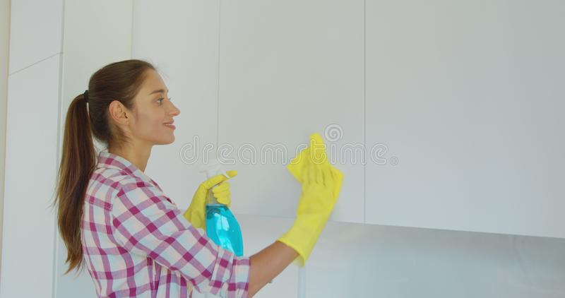 Woman`s hand in a yellow rubber glove cleans the shiny surface of a modern plastic kitchen Cabinet with a cloth. The stock photo