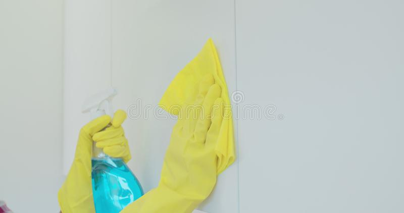 Woman`s hand in a yellow rubber glove cleans the shiny surface of a modern plastic kitchen Cabinet with a cloth. The royalty free stock image