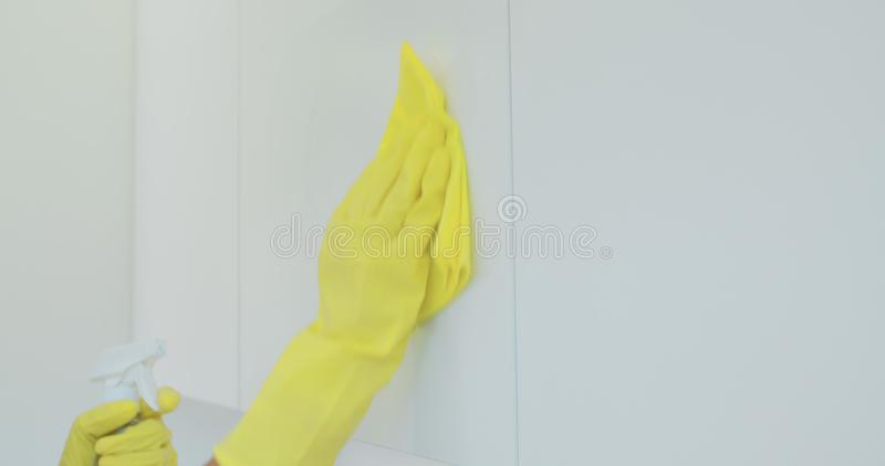 Woman`s hand in a yellow rubber glove cleans the shiny surface of a modern plastic kitchen Cabinet with a cloth. The. Concept of spring cleaning and home work royalty free stock photo