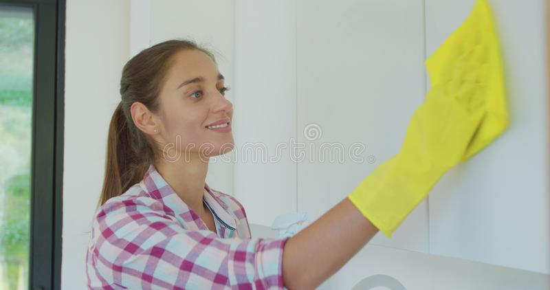 Woman`s hand in a yellow rubber glove cleans the shiny surface of a modern plastic kitchen Cabinet with a cloth. The royalty free stock photo
