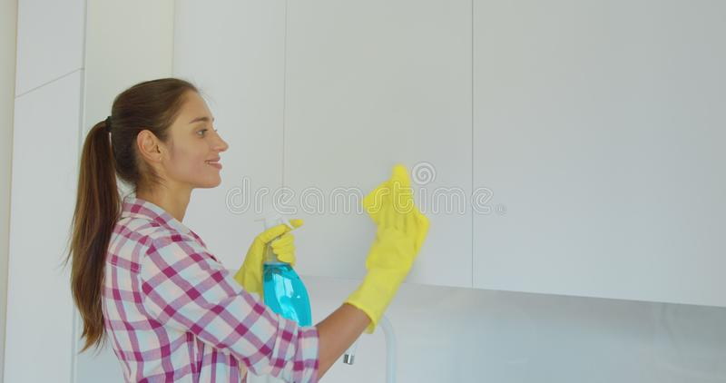 Woman`s hand in a yellow rubber glove cleans the shiny surface of a modern plastic kitchen Cabinet with a cloth. The stock photos