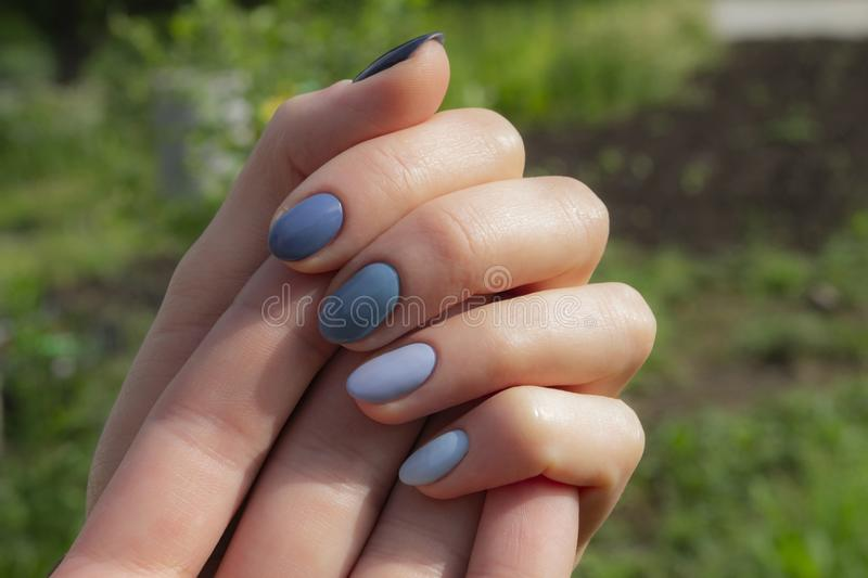 Woman`s hands with blue manicure on blurred background royalty free stock images