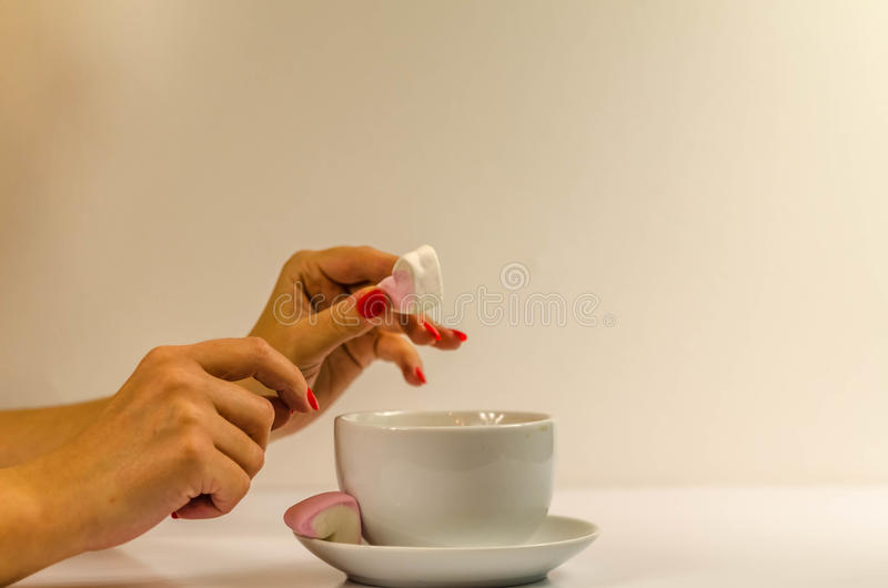 Woman`s hands with coffee cup. Heart, marshmallow, woman with red nails stock photography
