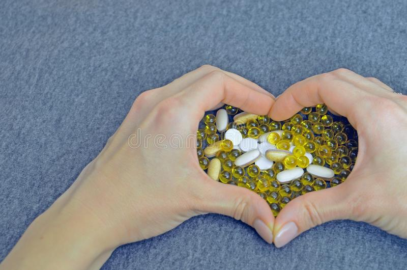 Woman`s hands created a heart shape. White and yellow pills. Mock up for special offers as advertising. Medical and royalty free stock photo