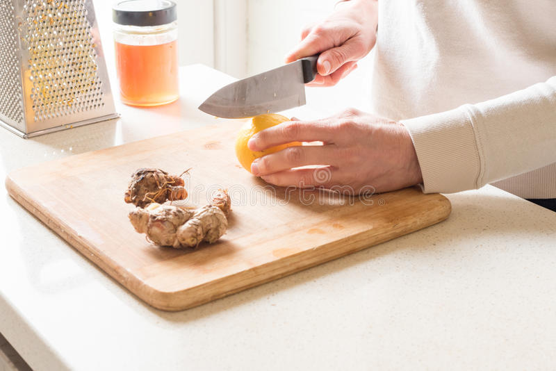 Woman's hands cutting lemon royalty free stock photography