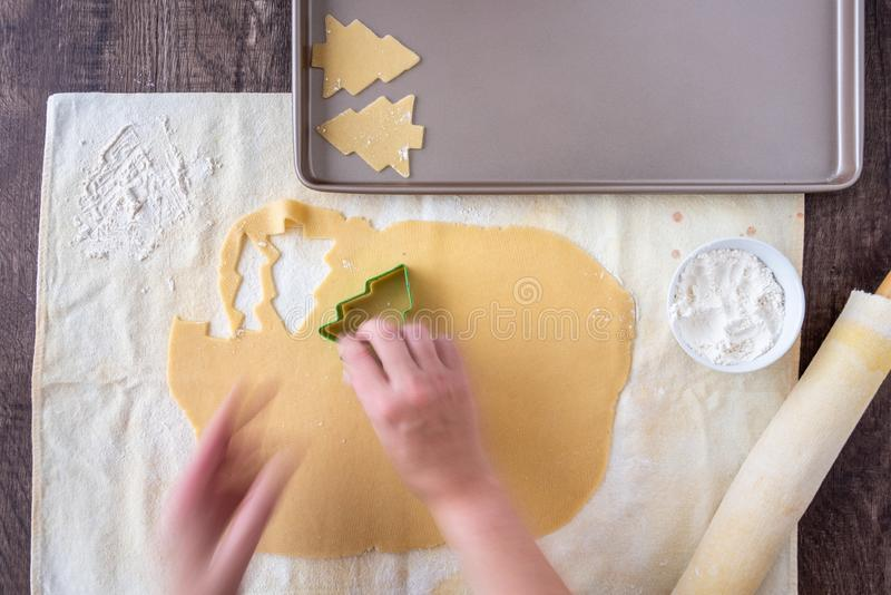 Woman's hands cutting out Christmas tree sugar cookies, pastry cloth, cookie sheet royalty free stock photography