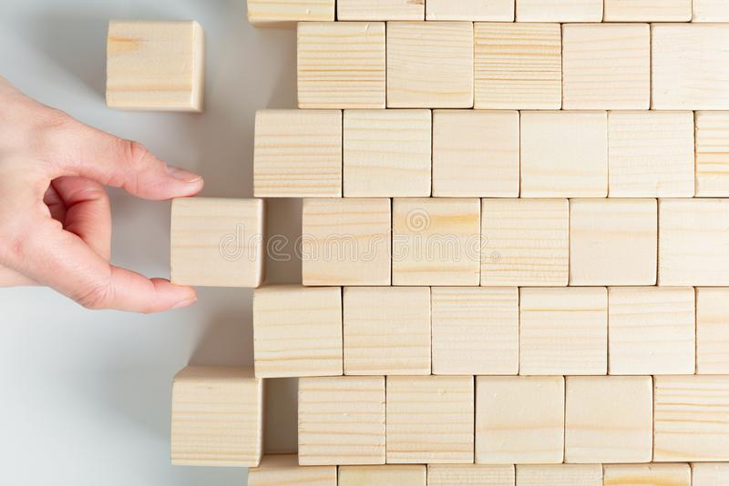 Woman`s hands finishing wooden cube pattern. Placing missing piece royalty free stock photography