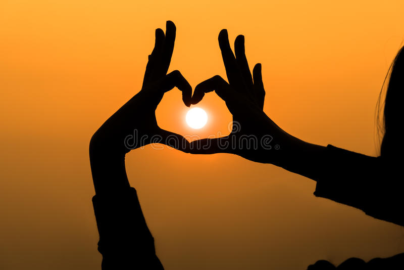 Woman's hands forming a heart shape with sunset silhouette royalty free stock photo