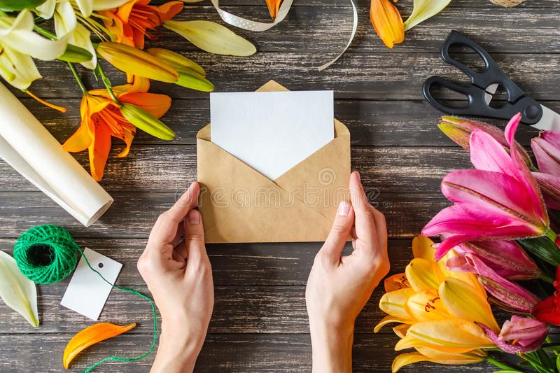 Woman`s hands hold craft envelope with empty white card for text royalty free stock image