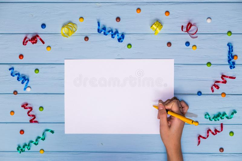 Woman`s hands hold pen and writing on white blank paper with colorful ribbons around. On blue wooden table. Office composition stock photo
