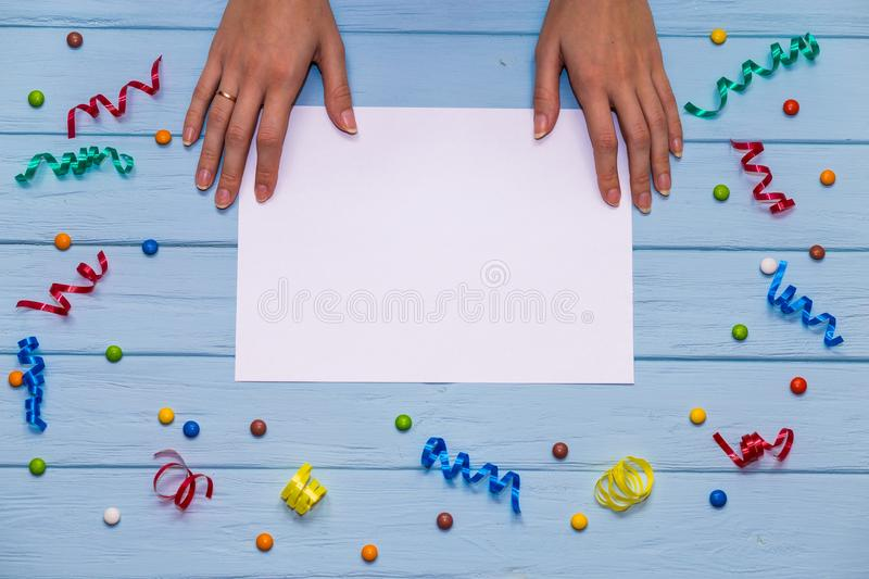Woman`s hands hold pen and writing on white blank paper with colorful ribbons around. On blue wooden table. Office composition royalty free stock photos