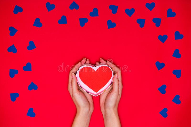 Woman`s hands hold red heart on red background royalty free stock image