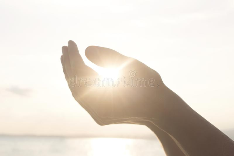Woman`s hands hold the sun and its energy. In the sunset royalty free stock photos