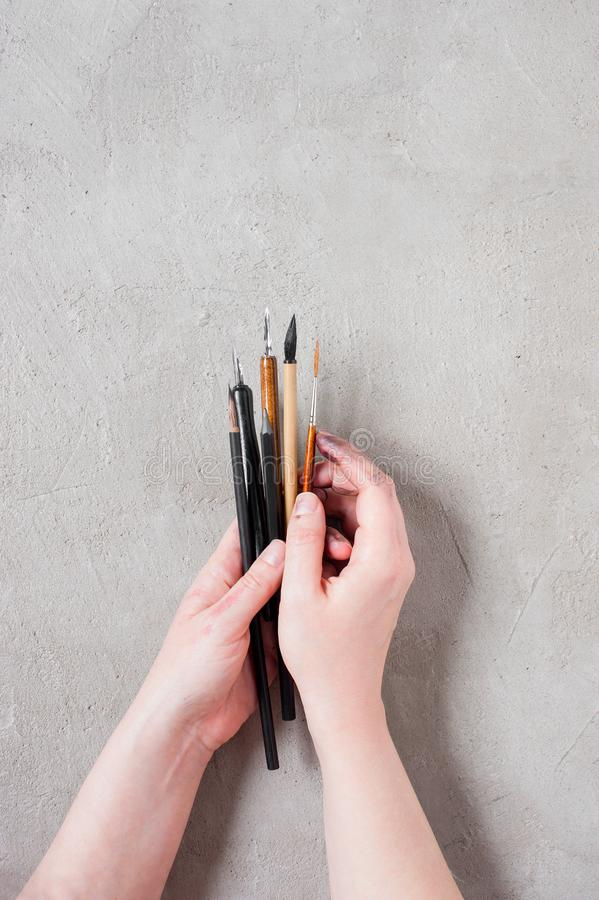 Woman`s hands holding the art brushes and ink pens. On the textured grey table, top view royalty free stock images