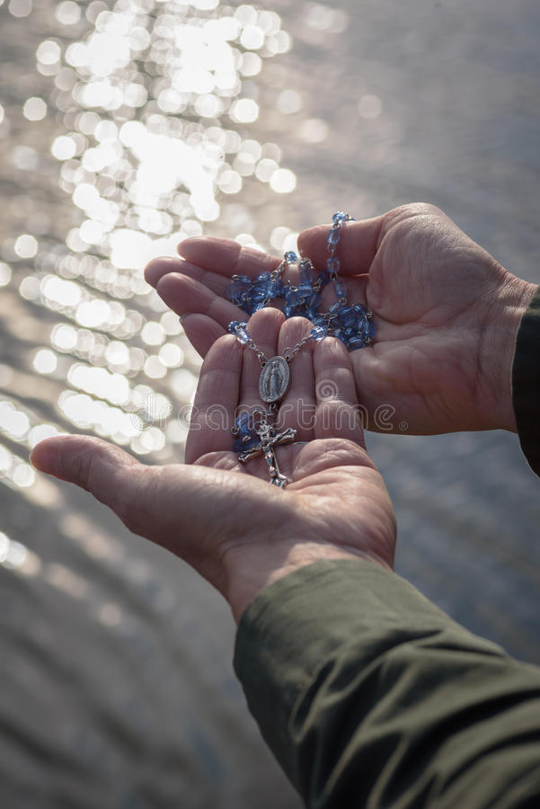Womans hands holding a blue rosary and cross extending over lake at sunset with sun reflecting on surface royalty free stock image