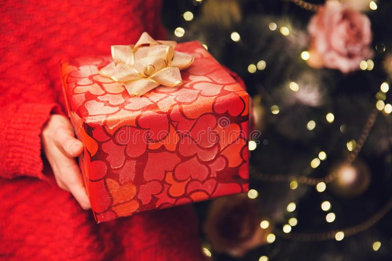 Woman`s hands holding Christmas or New Year decorated gift box. royalty free stock photo