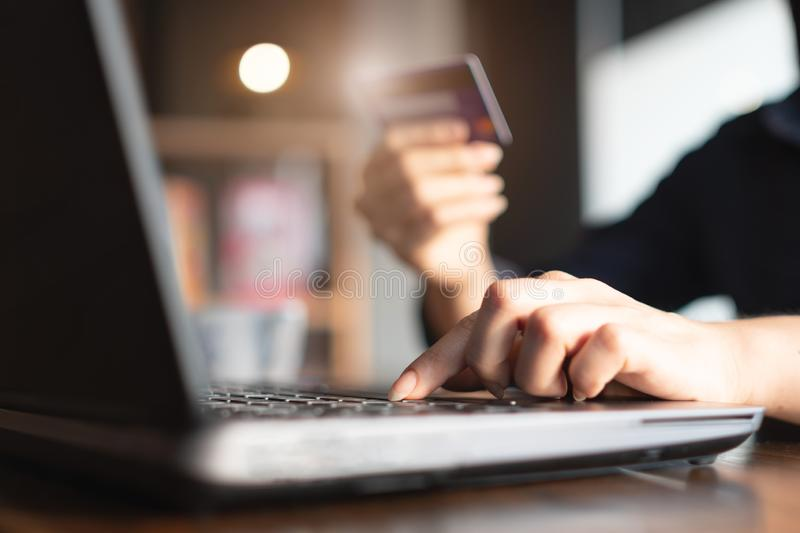 Woman`s hands holding credit card and typing on the keyboard of laptop for shopping online. Pays for purchase.  stock image