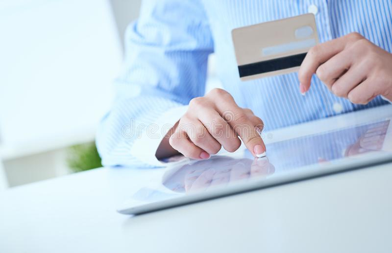 Woman`s hands holding a credit card and using tablet pc for online shopping. Middle section of young businesswoman royalty free stock image