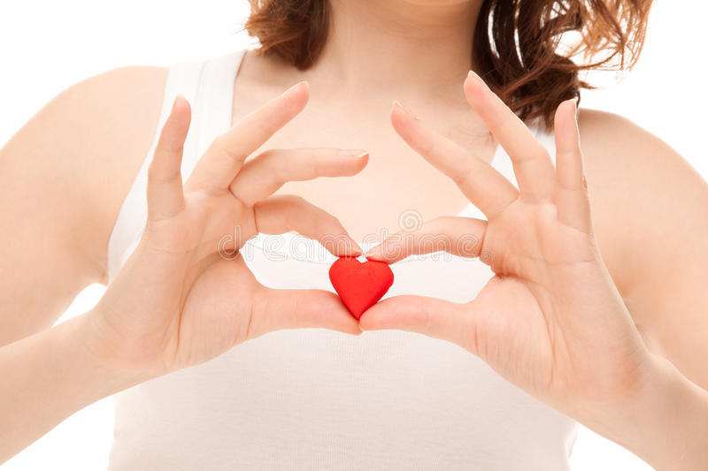 Woman's hands holding heart-shaped cookie. Isolated on white stock photo