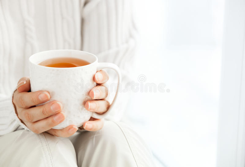 Woman`s hands is holding hot cup of coffee or tea in morning su stock photo