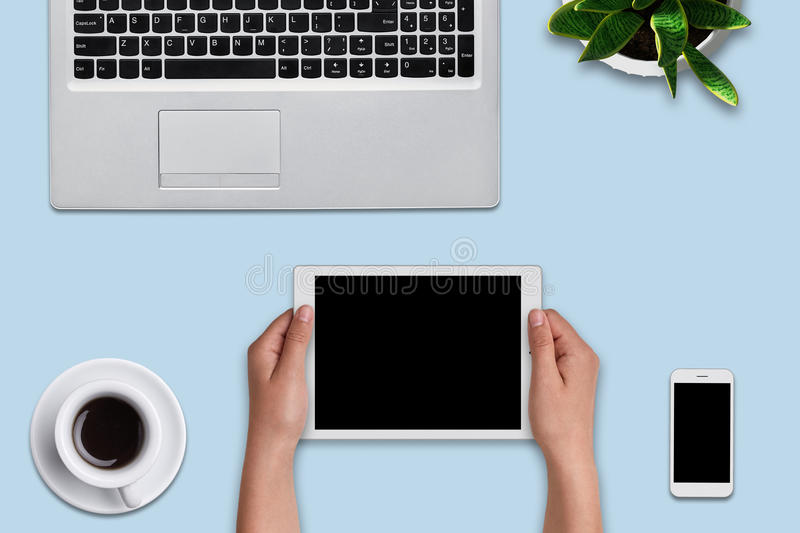Woman`s hands holding modern tablet over blue background. Office desk with laptop computer, flower, cell phone, tablet and cup of. Coffee. Top view of modern royalty free stock image
