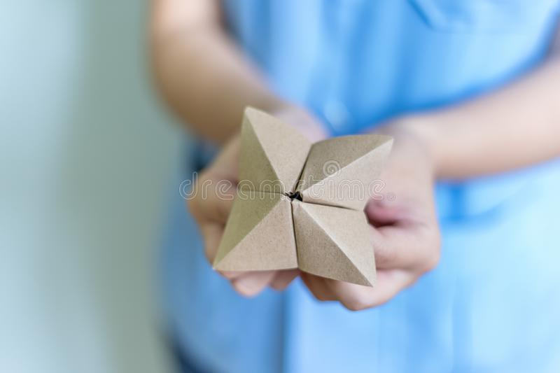 Woman`s hands holding a paper fortune teller stock photos