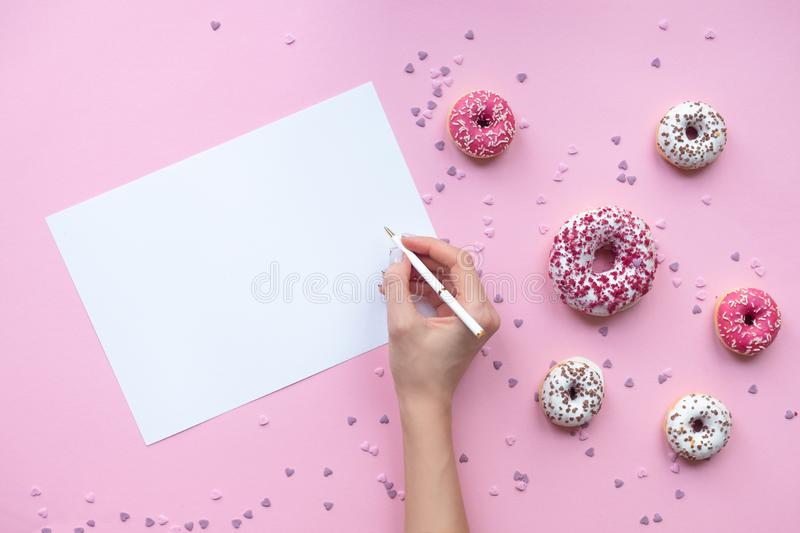 Woman`s hands holding pen. Pink background with donuts. Flat lay style stock image