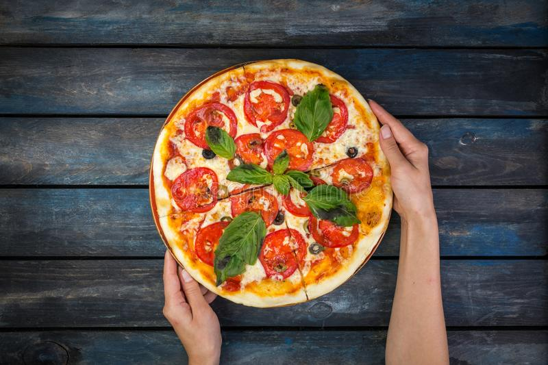 Woman`s hands holding a perfect pizza margarita with tomato slices, olives and basil leaves. Top view stock photos