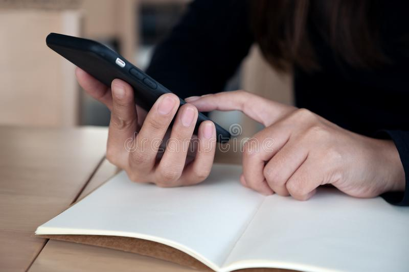 Woman`s hands holding and pointing at smart phone with notebook on wooden table. Closeup image of woman`s hands holding and pointing at smart phone with notebook stock photo