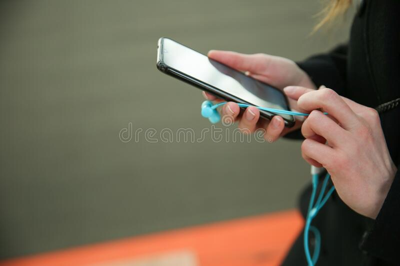 Woman`s hands holding smartphone and earphones. Close-up with copy space stock image