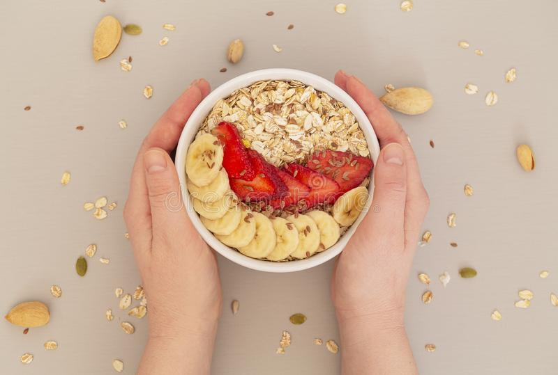 Woman`s Hands holding Smoothie bowl with muesli, strawberries, banana slices and flax seed. stock image