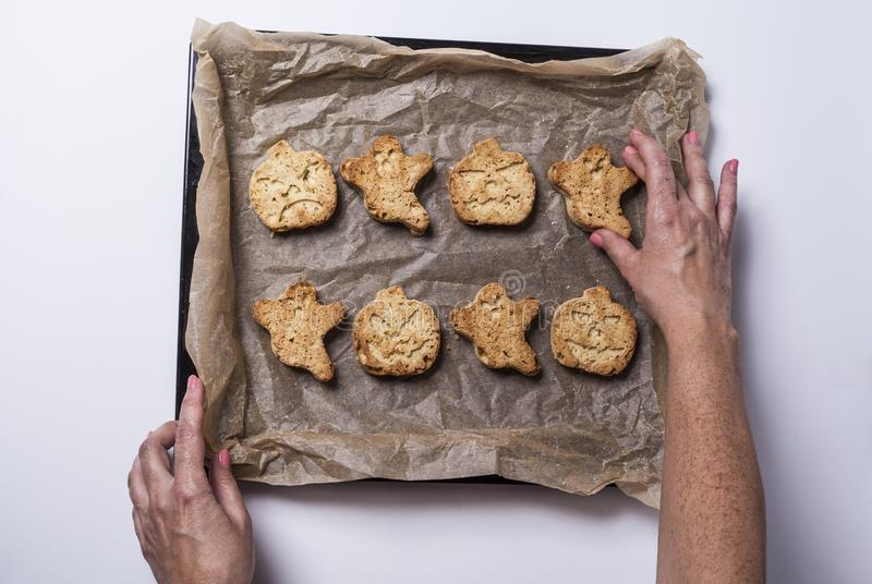 Halloween cookies. Woman& x27;s hands holding a tray of halloween cookies freshly baked from the oven royalty free stock photos