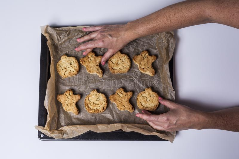 Halloween cookies. Woman& x27;s hands holding a tray of halloween cookies freshly baked from the oven stock image