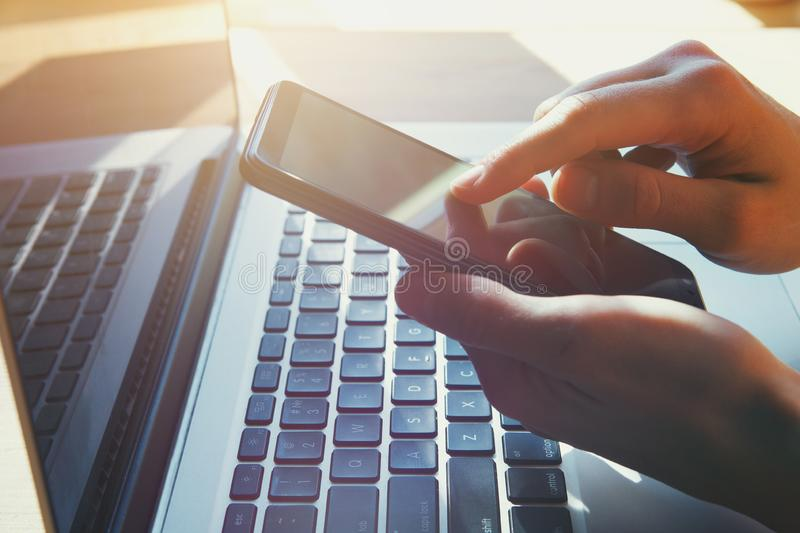 Woman`s hands holding and using smart phone, touching screen and working on laptop, stock photo
