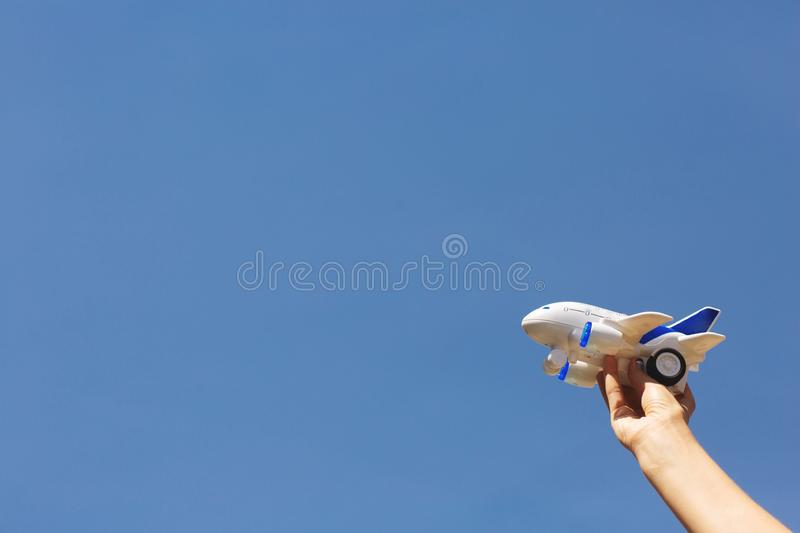 Woman`s hands holding a white and blue children`s airplane. Blue sky background stock photos