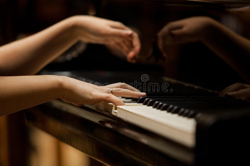 Woman's hands on the keyboard of the piano closeup. In dark colors royalty free stock photos