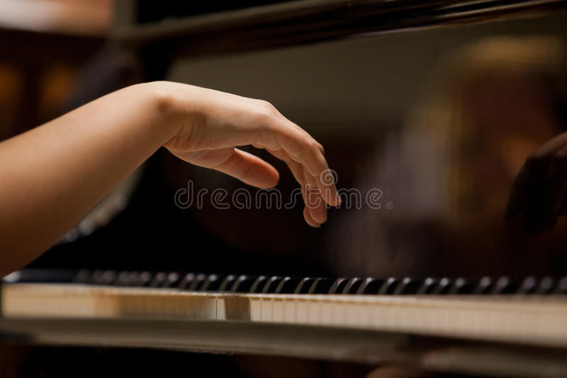 Woman's hands on the keyboard of the piano closeup. In dark colors stock photo