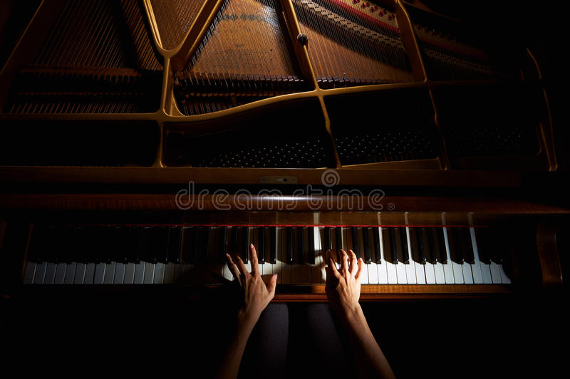 Woman's hands on the keyboard of the piano in night closeup stock photography