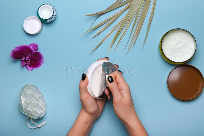 Woman`s hands are opening new jar of cream on blue background with cosmetic products jars royalty free stock photo