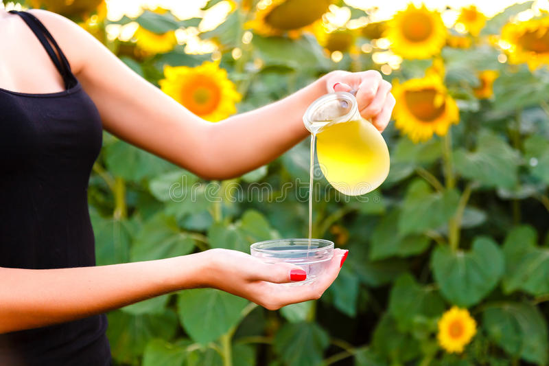 Woman's hands pours sunflower oil from the jar. Woman's hands pours a sunflower oil from the jar royalty free stock photography