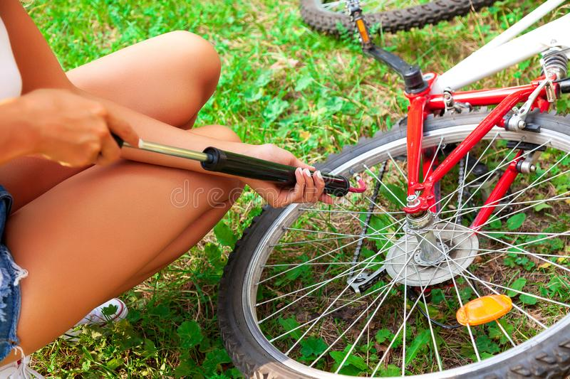 Woman`s hands pumping up a bike tire using small hand pump. Closeup shot of woman`s hands pumping up a bike tire using small hand pump stock photography