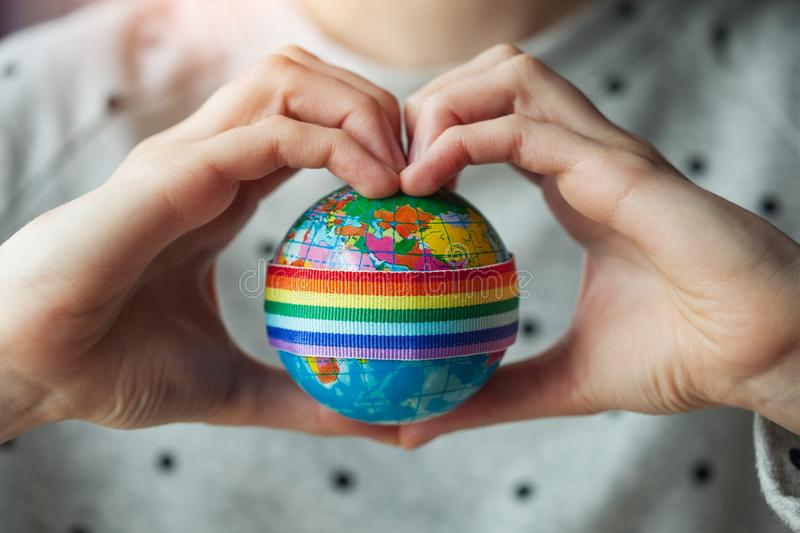 Woman`s hands in shape of heart holding globe with LGBT rainbow ribbon. Lesbian, gay couple and love concept, LGBT marriage stock photography