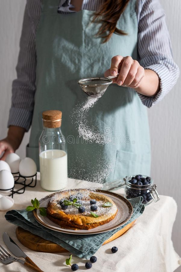 Woman`s hands sprinkling powdered sugar on a Homemade Dutch Baby Pancake with Blueberries, mint and Powdered Sugar. Delicious. Pancake, blueberries, bottle of royalty free stock photography